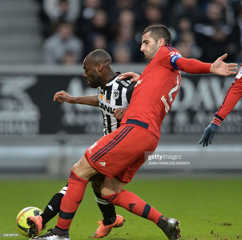 Angers' French forward Gilles Sunu (L) vies for the ball with Lyon's French midfielder Maxime Gonalons during the French L1 football match between Angers (SCO) and Lyon (OL), on February 6, 2016, in Jean Bouin Stadium, in Angers, northwestern France. AFP PHOTO / JEAN-FRANCOIS MONIER / AFP / JEAN-FRANCOIS MONIER