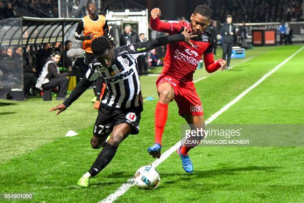 Angers' French forward Jonathan Bamba vies for the ball with Guingamp's French defender Marcus Coco during the French L1 football match between...