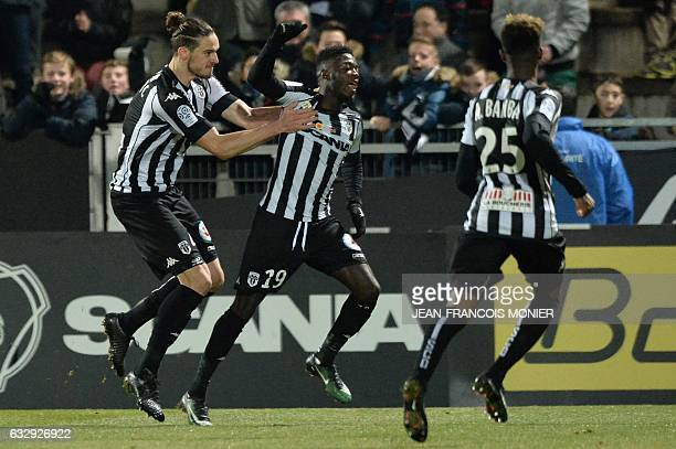 Angers' French forward Nicolas Pepe is congratulated by his teammates Angers' French defender Mateo Pavlovic after scoring a goal during the French...
