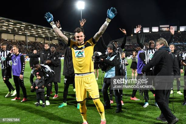 Angers' French goalkeeper Alexandre Letellier and his teammates react after wining the French Cup semifinal match between Angers and EA Guingamp on...