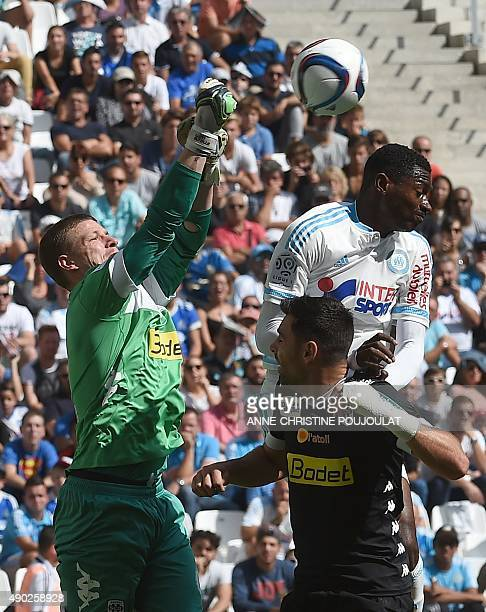 Angers' French goalkeeper Ludovic Butelle and Angers' French midfielder Thomas Mangani vie with Marseille's Cameroonian midfielder AndreFrank Zambo...