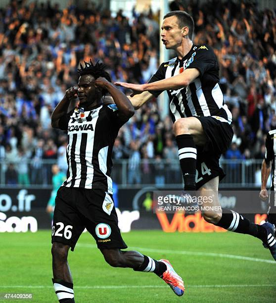 Angers' French midfielder Guy Adolphe Ngosso is congratulated by Angers' French defender Romain Thomas after scoring a goal during the French L2...