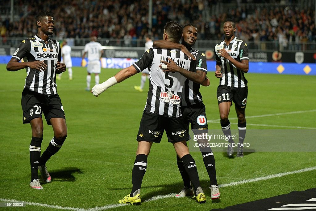 Angers' French midfielder Thomas Mangani is congratulated by his teammates on scoring on a penalty during the French L1 football match between Angers...