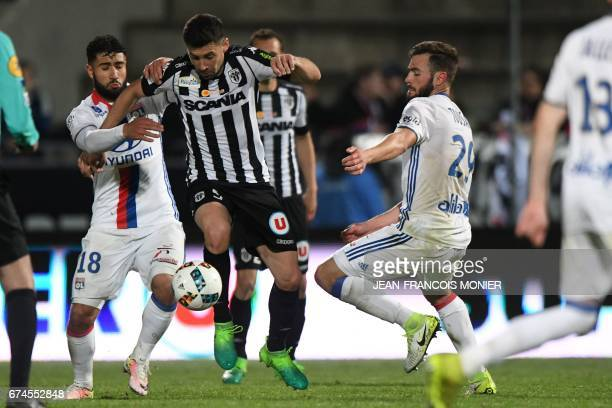 Angers' French midfielder Thomas Mangani vies for the ball with Lyon's French midfielder Nabil Fekir and Lyon's French defender Lucas Tousart during...