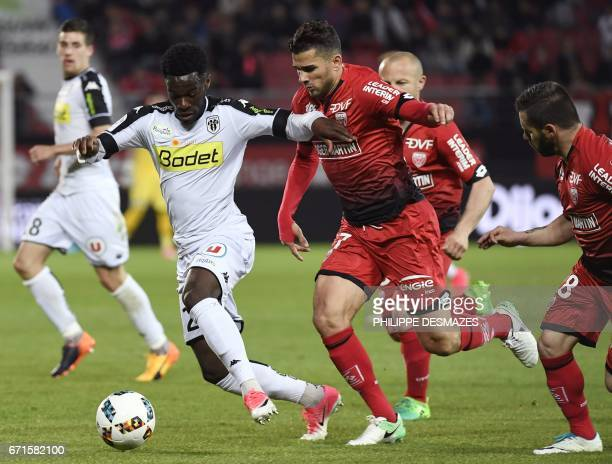 Angers' French midfielder Yohann Eudeline vies with Dijon's Algerian midfielder Mehdi Abeid and Dijon's French midfielder Frederic Sammaritano during...