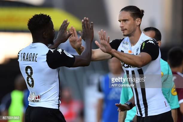 Angers' Ivorian defender Ismael Traore high fives Angers' French defender Mateo Pavlovic during the French L1 football match between Angers and...