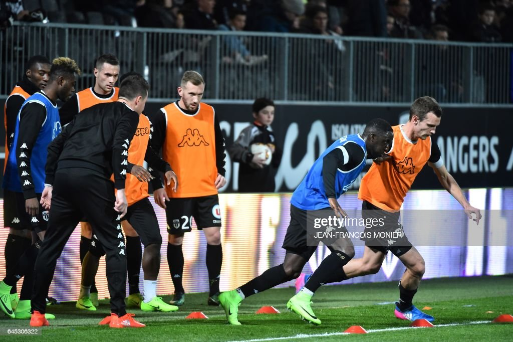 Angers' Senegalese defender Issa Cissokho (L) and Angers' French defender Romain Thomas (R) warm-up before the French L1 football match between Angers (SCO) and Bastia (SC), on February 25, 2017, in Jean Bouin Stadium, in Angers, northwestern France. / AFP / JEAN