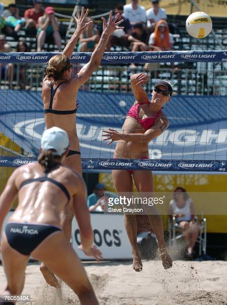 Angie Akers hits a shot past Nicole Branagh and Elaine Youngs during the Women's Main Draw at the Manhattan Beach Pier during the AVP Tour on August...