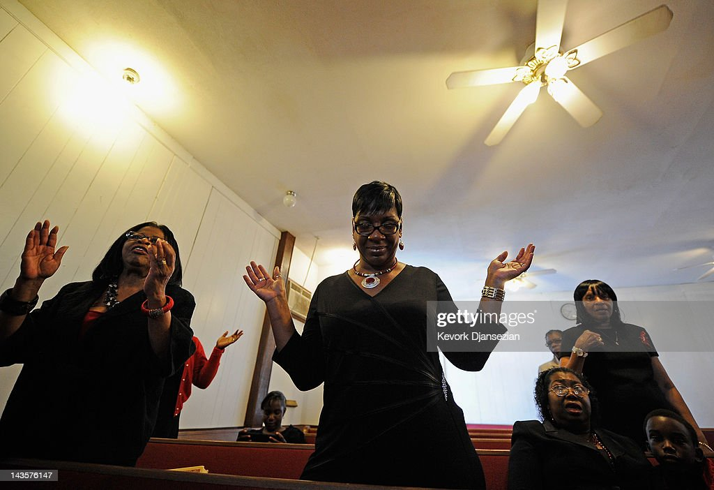 Angie Haywood (C) prays with fellow parishioners in the New Greater Peace Missionary Baptist Church in South Los Angeles on April 29, 2012 in Los Angeles, California. It's been 20 years since the verdict was handed down in the Rodney King case that sparked the infamous Los Angeles riots.