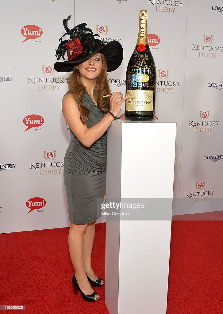 Angie Johnson signs the Moet & Chandon 6L for the Churchill Downs Foundation during the 139th Kentucky Derby at Churchill Downs on May 4, 2013 in Louisville, Kentucky.