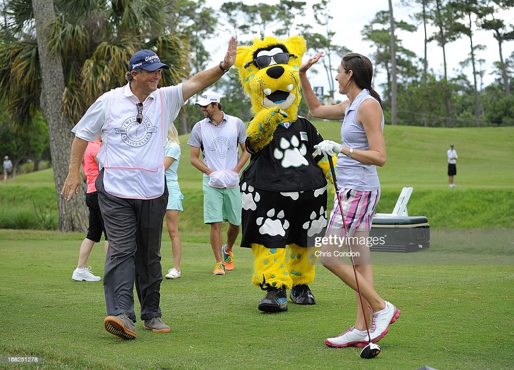 Angie Oberholser high fives with Peter Jacobsen along with Jacksonville Jaguars mascot Jaxson DeVille on the first hole during PGA TOUR Wives Classic golf tournament held on Dye's Valley course before THE PLAYERS Championship on THE PLAYERS Stadium Course at TPC Sawgrass on May 7, 2013 in Ponte Vedra Beach, Florida.