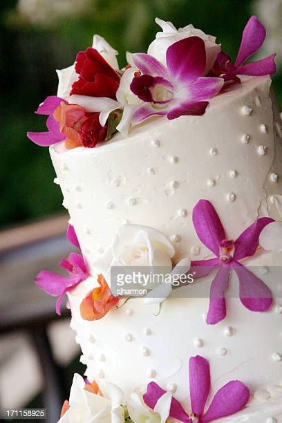 Angled Close-up of Flowers Decorating White Tiered Wedding Cake