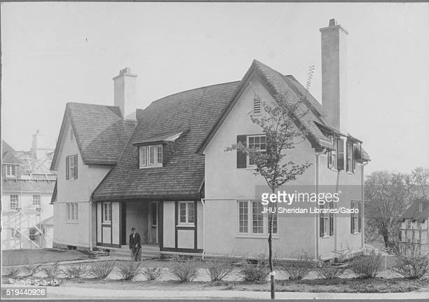 Angled frontal view of home next to quiet street lined with small bushes and young trees surrounded by other homes appears to be two stories tall...