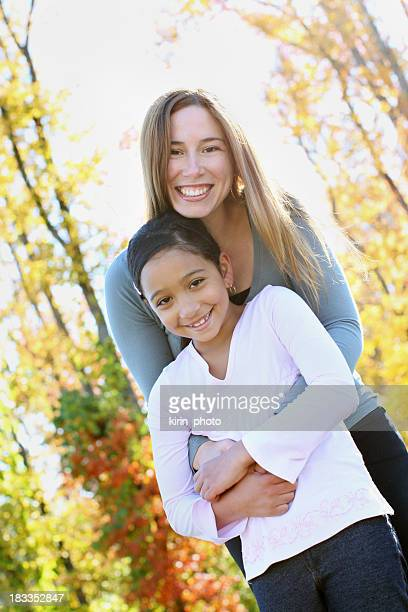 Angled outdoor portrait of mother and daughter embracing