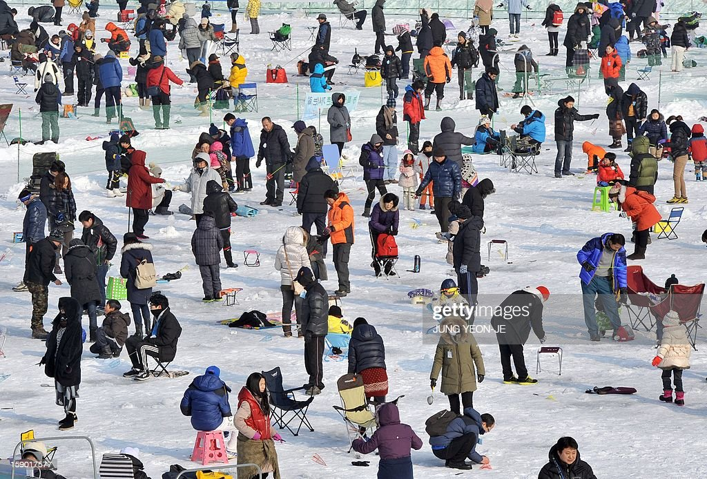 Anglers cast lines through holes created in the surface of a frozen river during an ice fishing contest in Hwacheon, 120 kilometers northeast of Seoul, on January 6, 2013. The contest is part of an annual ice festival which draws over 1,000,000 visitors every year. AFP PHOTO / JUNG YEON-JE