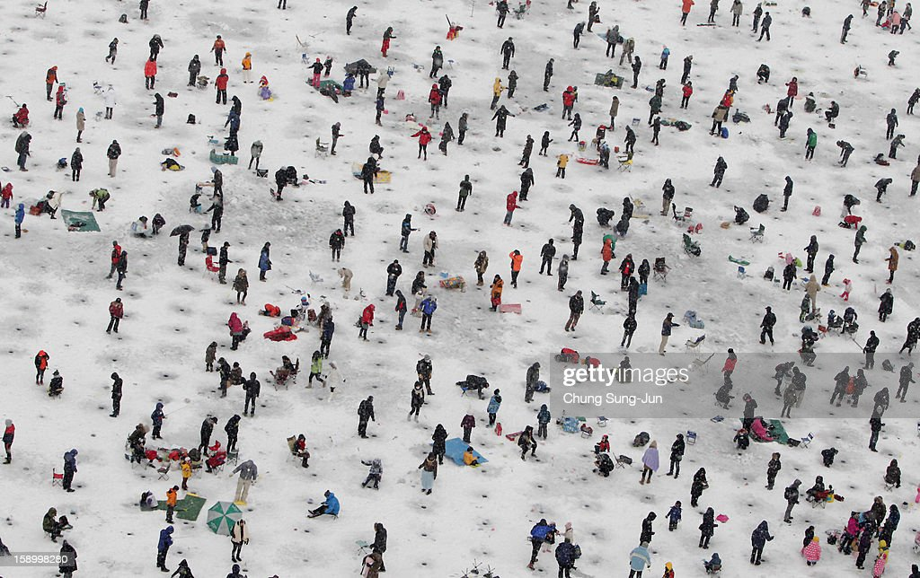 Anglers cast lines through holes into a frozen river during an ice fishing competition at the Hwacheon Sancheoneo Ice Festival on January 5, 2013 in Hwacheon-gun, South Korea. The annual event attracts thousands of visitors and features a mountain trout ice fishing competition in which participants compete with tradition lures or with bare hands.