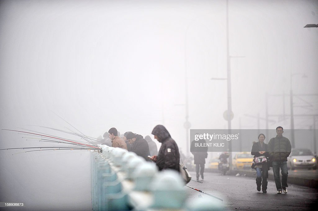 Anglers try to catch fish on Galata bridge in a heavy fog on the Galata Bridge early on January 4, 2013, in Istanbul over the Bosphorus.