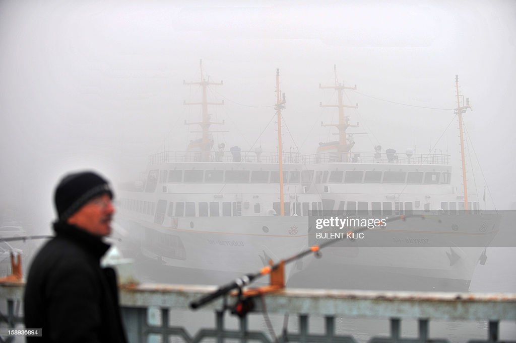 Anglers try to catch fish on Galata bridge in a heavy fog on the Galata Bridge early on January 4, 2013, in Istanbul over the Bosphorus. River traffic was brought to a halt this morning due to fog conditions. AFP PHOTO/BULENT KILIC