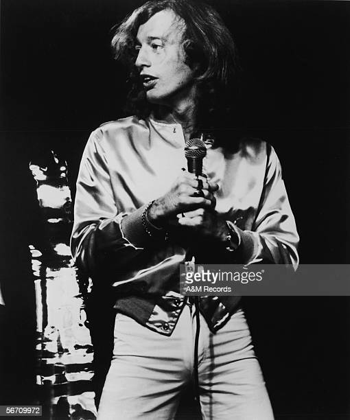 AngloAustralian singer Robin Gibb of the pop and disco group The Bee Gees wears a satin jacket as he sings on stage during a concert in a publicity...