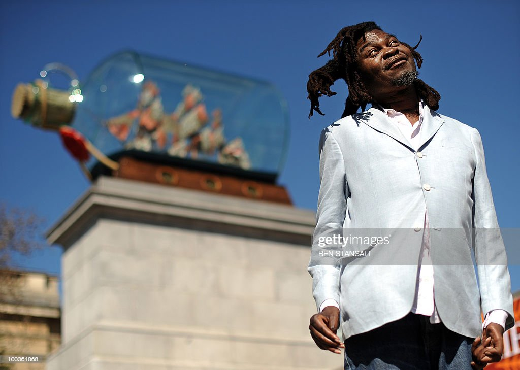 Anglo-Nigerian contemporary artist Yinka Shonibare poses for pictures beside his artwork entitled 'Nelson's Ship in a Bottle' following its unveiling on the fourth plinth in Trafalgar Square in London, on May 24, 2010. The artwork featues a large scale model of the ship HMS Victory, from which Horatio Nelson commanded the Battle of Trafalgar in 1805.