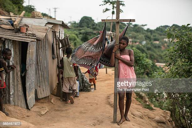 A girl stands beside a laundry line in a poor neighborhood overlooking Cabinda a heavily guarded territory that accounts for half the oil output from...