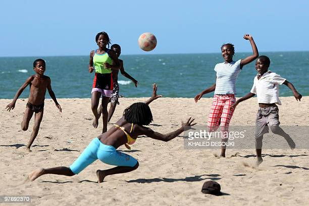 Angolan girls and boys enjoy playing football on the Atlantic ocean beach in Benguela on January 18 2010 during the African Nations Cup football...