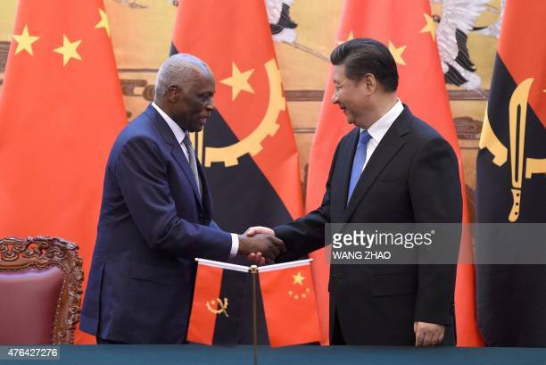 Angolan President Jose Eduardo Dos Santos shakes hands with Chinese President Xi Jinping during a signing ceremony at the Great Hall of the People in...