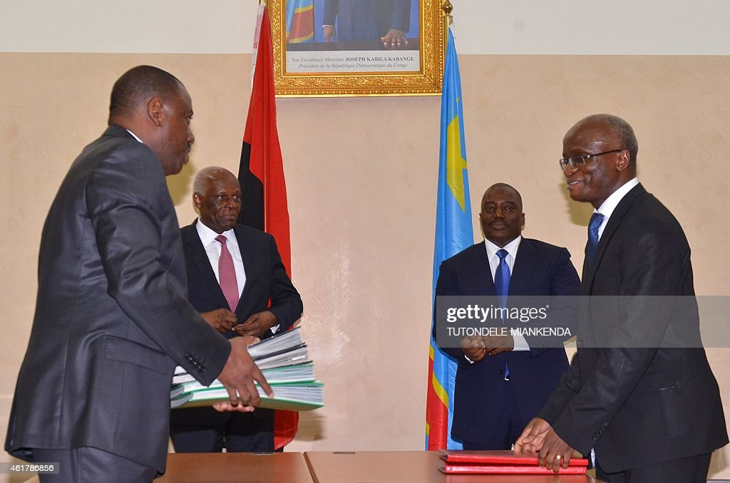 Angola's Transports Minister Augusto Da Silva (L) and his Congolese counterpart Justin Kalumba Mwana Ngongo (R) smile after signing agreements on transports, next to Democratic Republic of Congo's President <a gi-track='captionPersonalityLinkClicked' href=/galleries/search?phrase=Joseph+Kabila&family=editorial&specificpeople=467567 ng-click='$event.stopPropagation()'>Joseph Kabila</a> (2ndR) and Angola's President Jose Edouardo Dos Santos (2ndL) look on, on January 19, 2015 in Kinshasa. Three people were killed in Kinshasa on Monday in clashes between police and thousands protesting moves to allow President <a gi-track='captionPersonalityLinkClicked' href=/galleries/search?phrase=Joseph+Kabila&family=editorial&specificpeople=467567 ng-click='$event.stopPropagation()'>Joseph Kabila</a> to extend his hold on power, a government source said. AFP PHOTO / TUTONDELE MIANKENDA