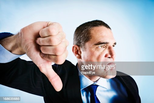 Angrily frowning businessman makes thumbs-down signal