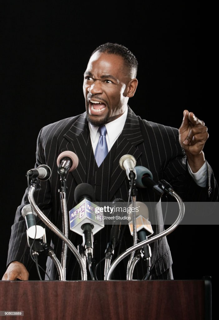 Angry African man gesturing at podium with microphones : Stock Photo