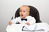 A cute Caucasian baby sitting in his high chair wearing a white shirt and a bow tie looking like a boss with pen and paper and yelling at somebody. Baby boss yelling at his subordinates. Funny little