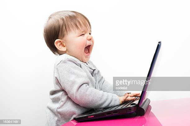 Angry baby girl using a laptop computer