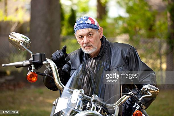 Angry Biker in leather jacket on motorcycle pointing toward camera