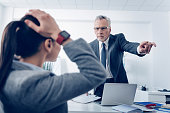 Get out of here. Selective focus on an extremely mad chief in glasses looking at his scared female employee with hands on the head and pointing toward a door while asking her to leave the office.