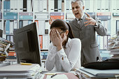 Angry boss yelling at his young employee, she is stressed and feeling frustrated: bullying boss and mobbing concept