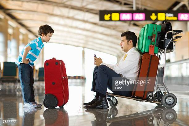 Angry Boy With Businessman at Airport Terminal