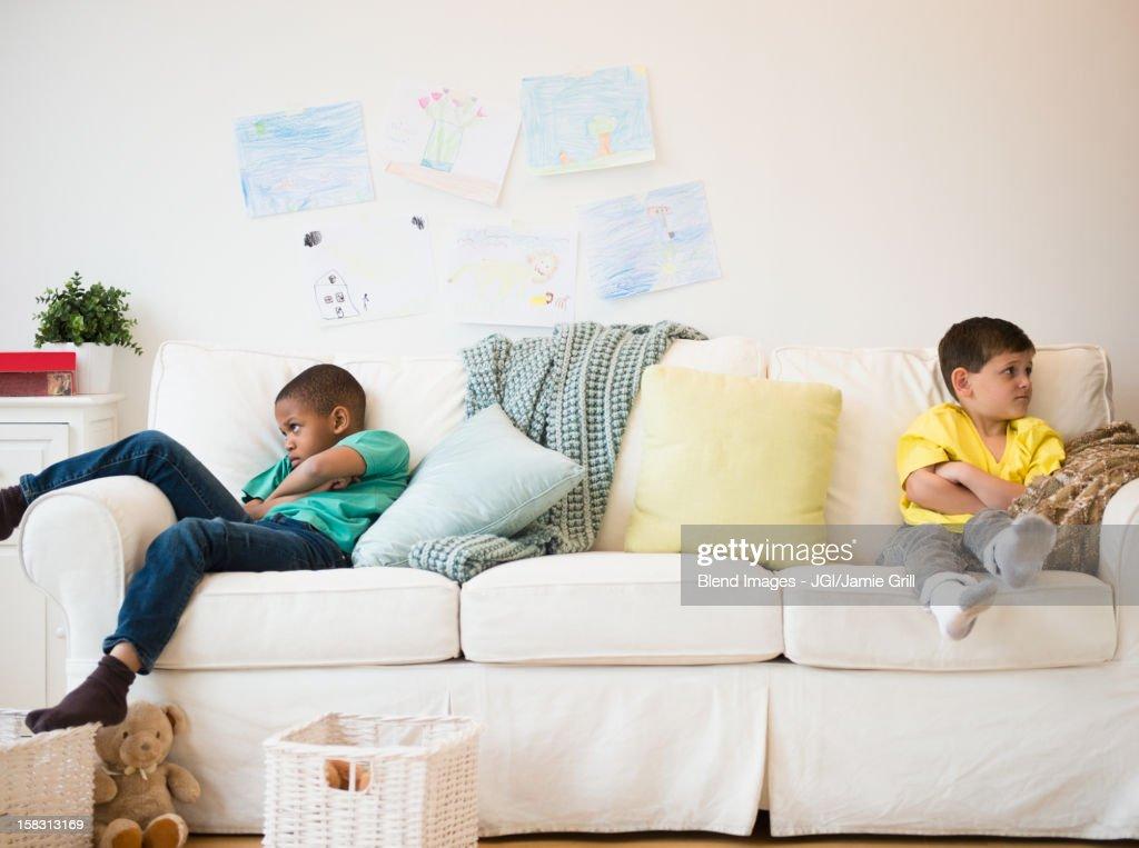 Angry boys sitting on sofa : Stock Photo