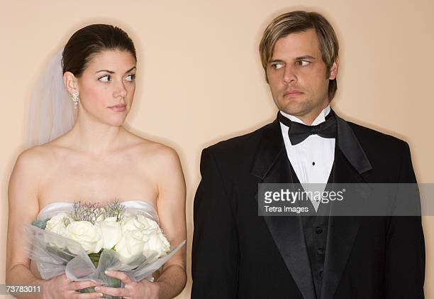 Angry bride and groom looking at each other