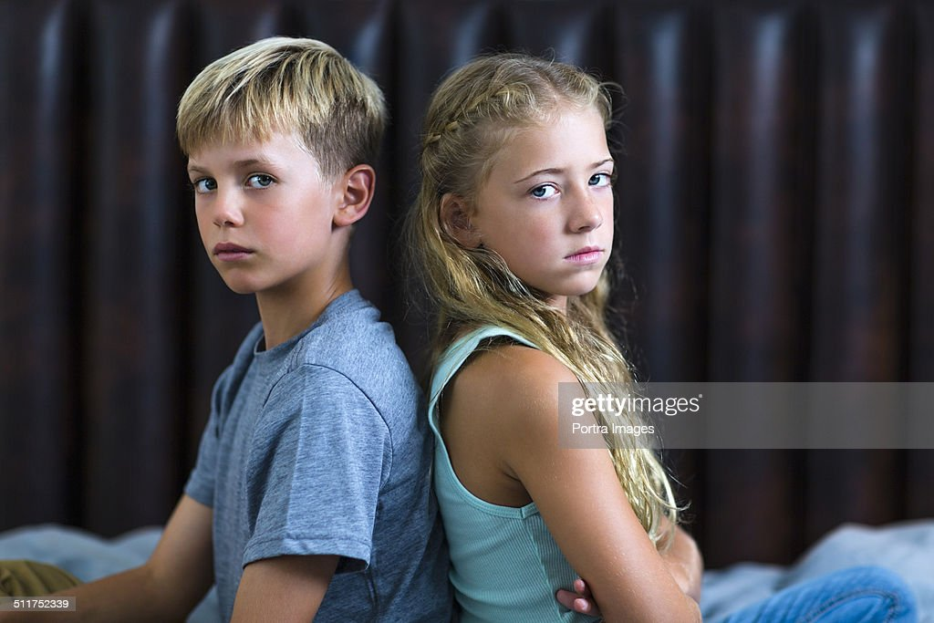 Angry brother and sister sitting back to back