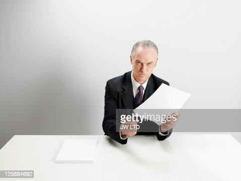 Angry businessman burning document with cigarette lighter : Stock Photo