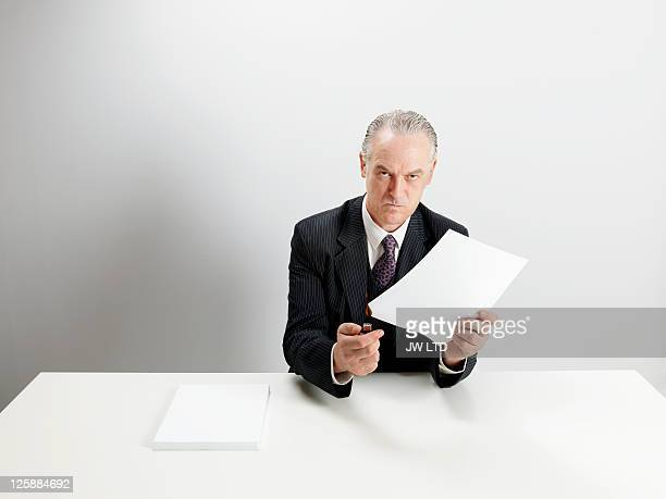 Angry businessman burning document with cigarette lighter