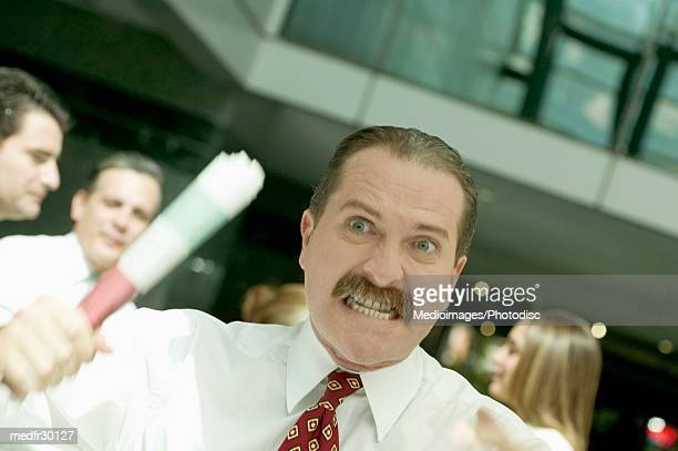 Angry businessman holding roll of paper with other business people talking in the background, close-up, tilt, selective focus