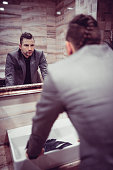 Angry Businessman Standing in the Restroom and Looking at Mirror
