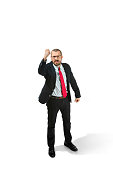 Angry aggressive businessman threatening by fist to camera. Isolated on white studio background. Serious bearded young man in glasses, suit, red tie. Business, threat, boss concept.