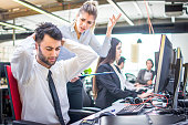 Angry businesswoman shouting at her worker with hands behind head in office