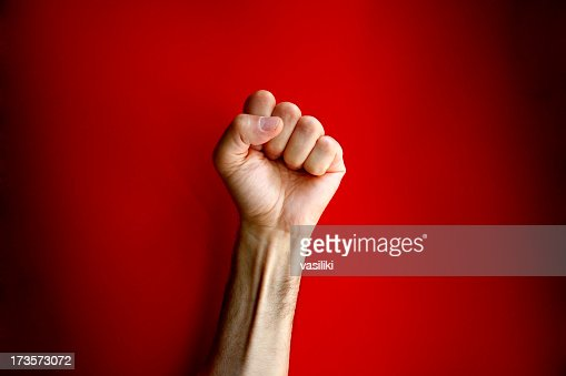 Angry clenched fist on red background