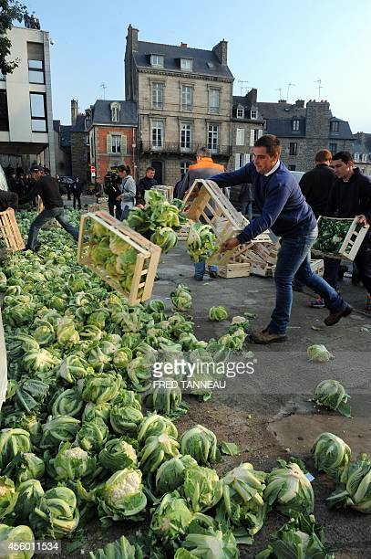 Angry farmers dump cauliflowers in front of the prefecture building of SaintBrieuc northwestern France as riot policemen onwatch on September 24 as...
