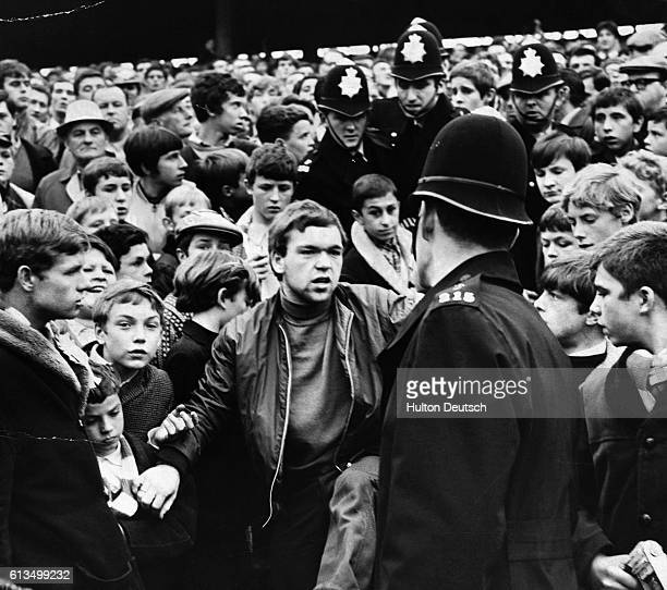 Angry football fans confront police during a match between Queens Park Rangers and Millwall