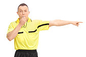 Angry football referee blowing a whistle and pointing with his hand isolated on white background