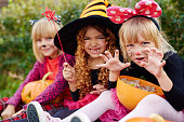 Three girls in Halloween costumes looking at camera